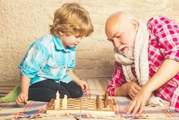 チェスをしている男の子と成熟した男