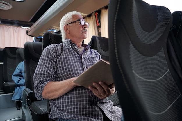 Зрелый мужчина с открытой книгой, глядя через окно