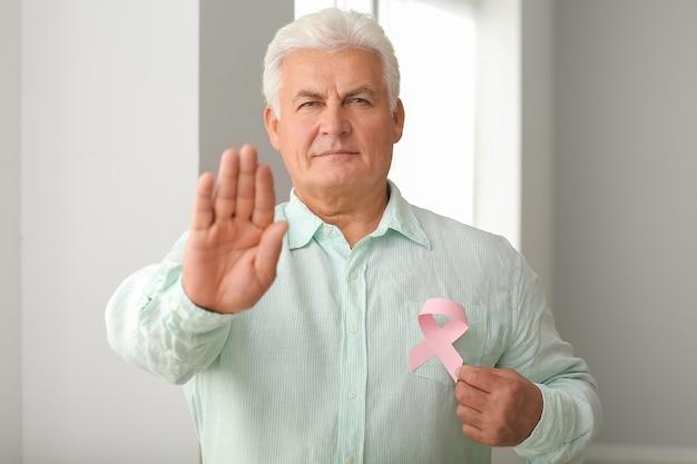屋内でピンクのリボンを持つ成熟した男。乳がんの意識の概念