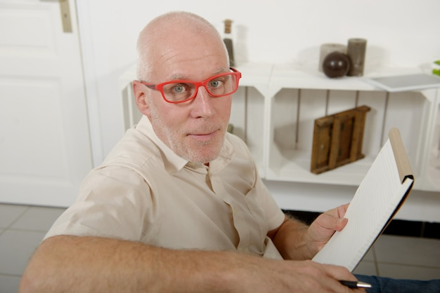 Mature man with red glasses using notebook