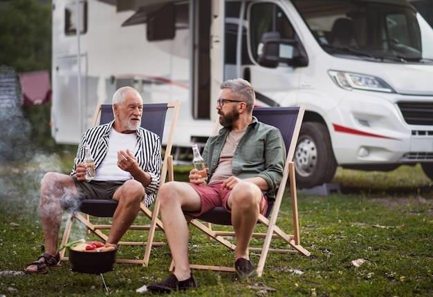 屋外のキャンプ場で話している先輩の父との成熟した男、キャラバンの休日の旅行でバーベキュー。