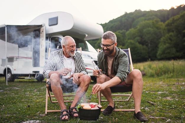 Зрелый мужчина со старшим отцом разговаривает в кемпинге на открытом воздухе с барбекю во время отпуска в караване