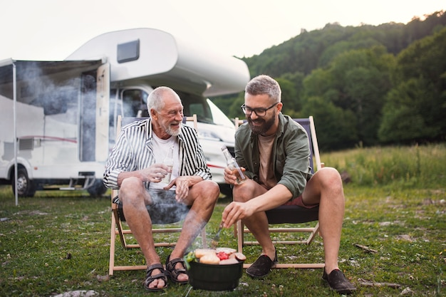 Mature man with senior father talking at campsite outdoors barbecue on caravan holiday trip