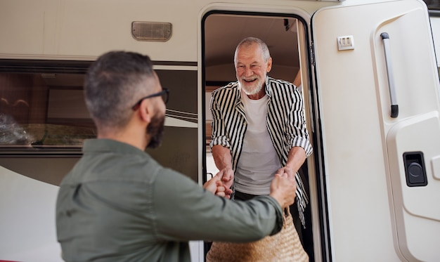 A mature man with senior father unpacking by car outdoors caravan holiday trip
