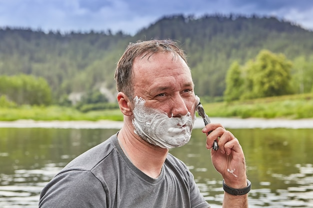 彼の顔にシェービングフォームを持つ成熟した男は、彼の休暇中に絵のように美しい川の横にある自然の中で朝に剃っています。