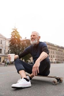 持続可能なモビリティスケートボードを持つ成熟した男