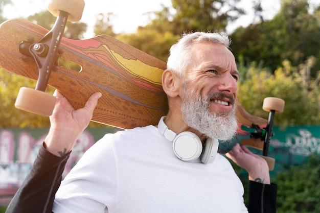 Uomo maturo con skateboard mobilità sostenibile