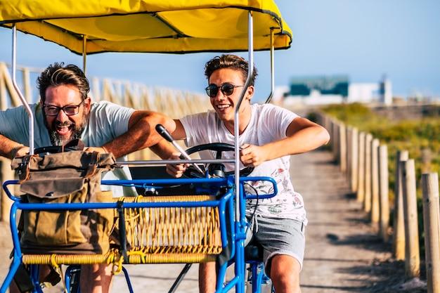 휴가 동안 도로에 카트를 타고 십대 아들과 성숙한 남자. 휴일에 여가를 즐기는 아버지 아들. 휴일에 트롤리 카트를 운전하는 재미 아들과 아버지