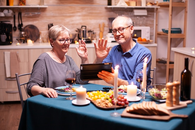 Mature man and woman waving at tablet pc during video conference in kitchen celebrating relationship. couple sitting at the table, browsing, talking, using internet, celebrating their anniversary in d