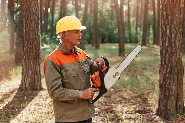 전기 톱으로 유니폼과 헬멧을 착용하는 성숙한 남자 나무꾼