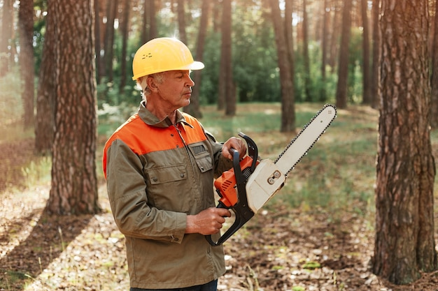 Mature man woodcutter wearing uniform and helmet with chainsaw