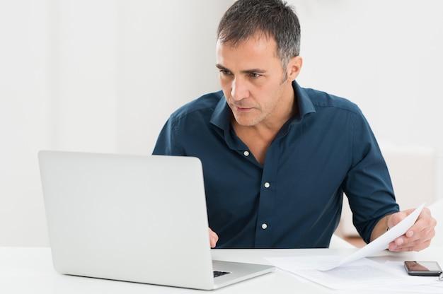 Зрелый человек, работающий на компьютере