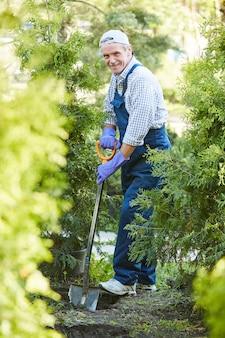 Зрелый человек, работающий в саду