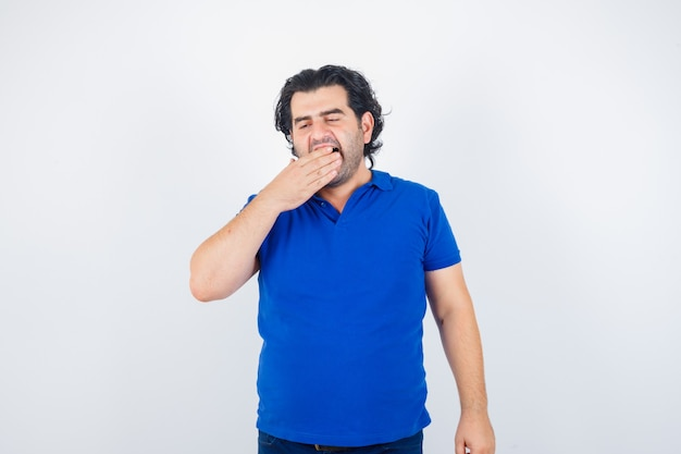 Mature man yawning in blue t-shirt and looking sleepy. front view.
