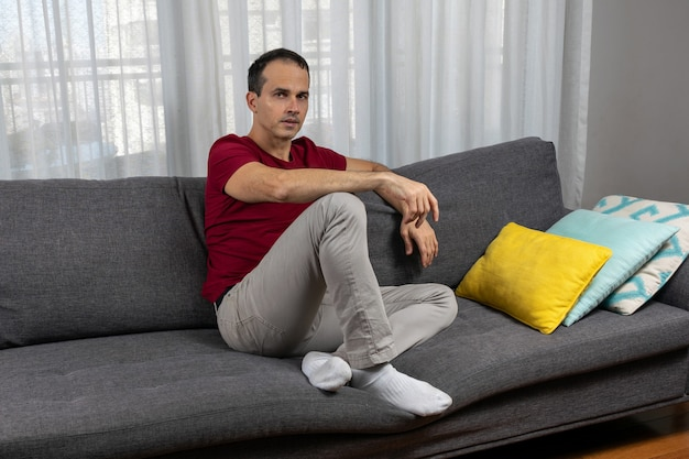 Зрелый мужчина лет сидит на диване с носками и рядом с красочными подушками.