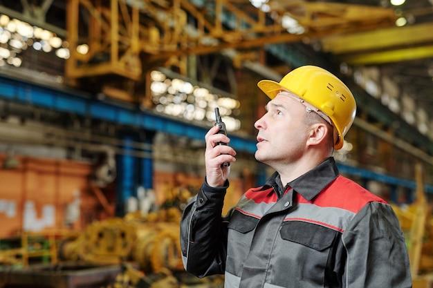 공장에서 자신의 작업에서 송신기를 사용하여 헬멧에 성숙한 육체 노동자