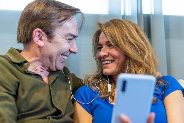 ヘッドフォンをつけて音楽を聴いている成熟した夫婦。高品質の写真