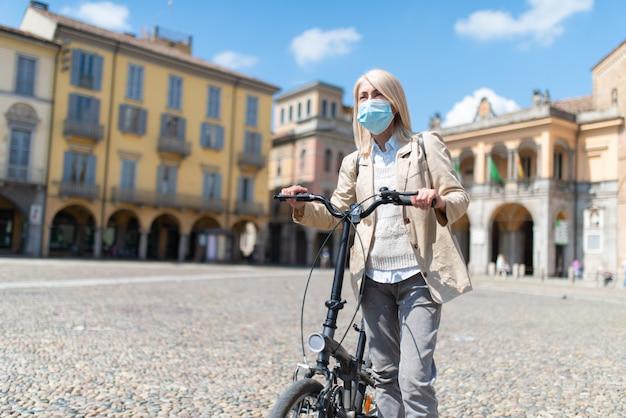 コロナウイルスのパンデミックの最中に都市で彼女の電動自転車に乗っている成熟したマスクされた女性