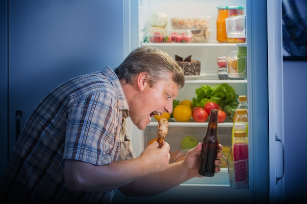 ビールとチキンの脚の冷蔵庫で成熟した男性