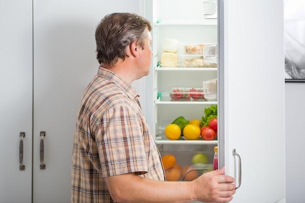 Mature men at fridge  with food