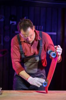 ジャンプスーツを着た成熟した中年男性が木工のプラスチック製のスケートボードをテストしています。