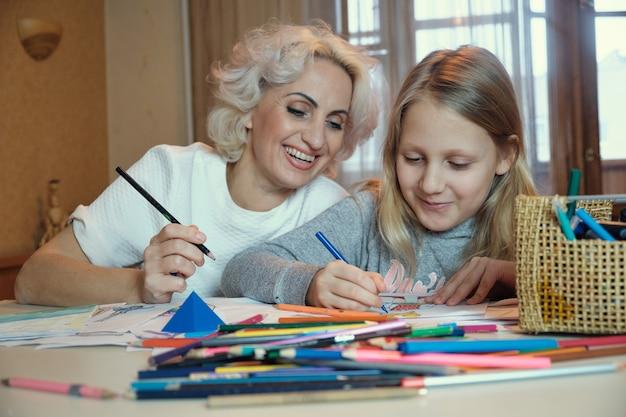 성숙한 어머니와 그녀의 작은 딸이 함께 그리기, 집에서 숙제, 선택적 집중