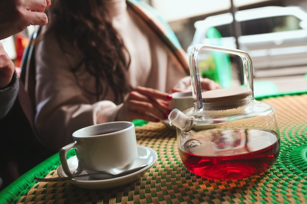 Mature mother and her young daughter sit together in cafe or restaurant. cut view picture of female's hands touching cup with hot tea. nice warm conversation. good relationships.