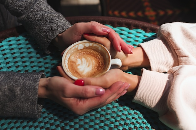 Mature mother and her young daughter sit together in cafe or restaurant. up view of female hands holding one cup of coffee together. love and support. family connection.