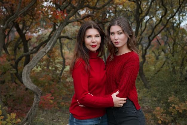 Зрелая мать обнимает с дочерью-подростком на природе в осенний день. осенняя мода, теплые красные свитера. прогулка в осеннем лесу