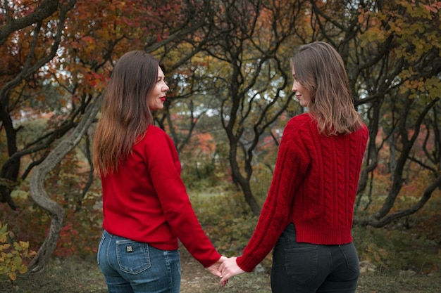 Mature mother hugging with her teen daughter outdoor in nature on autumn day. fall fashion, warm red sweaters. walking in autumn forest