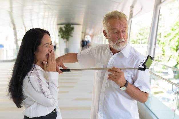 Пожилая многонациональная пара счастлива и влюблена во время знакомства с городом бангкок