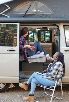 成熟した多民族の女性はキャンピングカーで自然の中でロードトリップ休暇を楽しんでいます