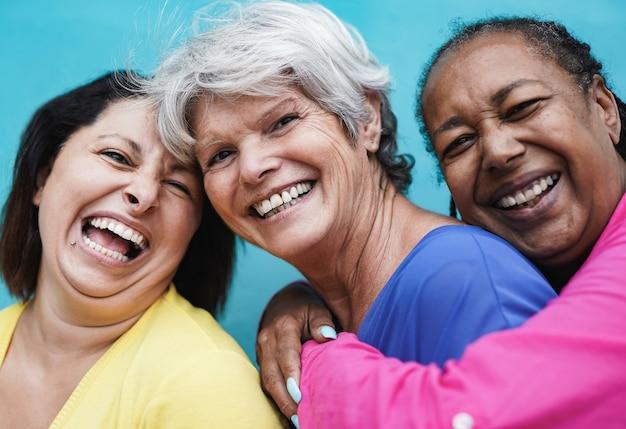 カメラで笑いながら青い背景で街で抱き合って成熟した多民族の女性-高齢者と友情の愛の概念
