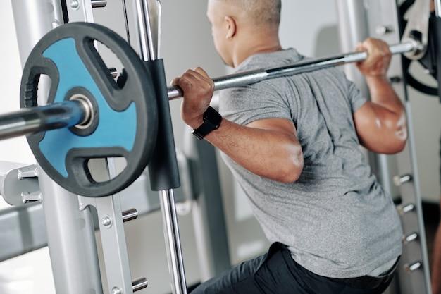 Зрелый мускулистый мужчина делает приседания со штангой с тяжелыми бортами