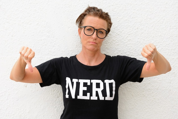Mature nerd woman wearing big eyeglasses and standing isolated