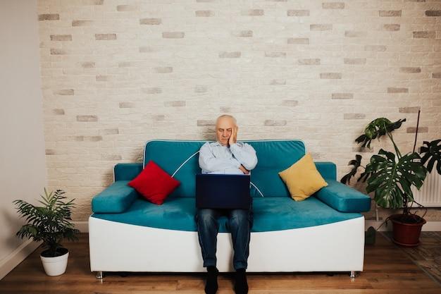 노트북을 장기간 사용한 후 피로로 고통받는 성숙한 노인. 가정에서 늦게까지 일하는 비즈니스 수석 남자.