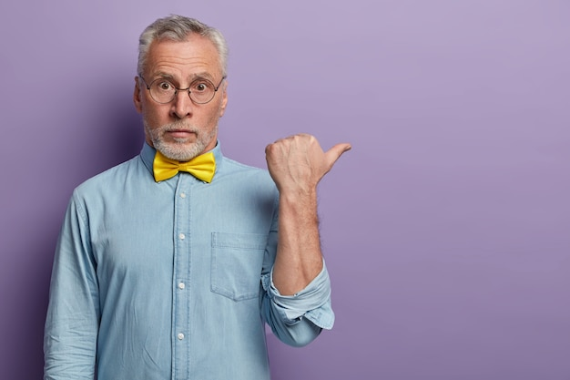 Mature old man with grey hair and beard points thumb aside, has surprised face expression, wears big round glasses