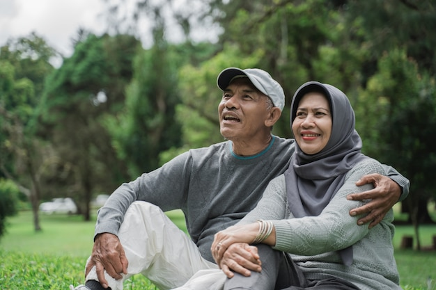 Mature old man and woman sitting on a grass in the park