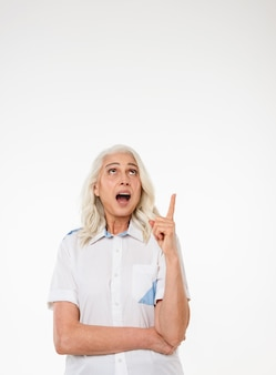Mature old shocked woman pointing.