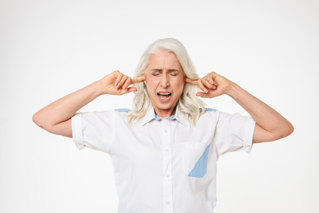 Mature old woman covering ears.