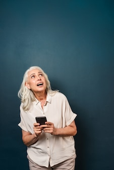 Mature old woman using mobile phone.
