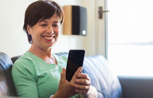 Зрелая пожилая женщина улыбается с помощью смартфона, сидя на диване у себя дома