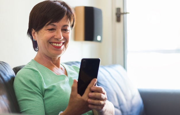 Mature older woman smiling using smartphone sitting on the sofa at home