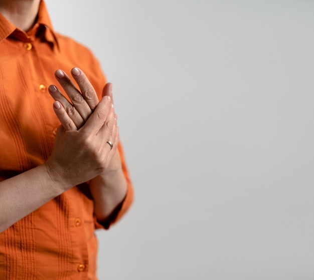 Mature in orange shirt cares for hands skin