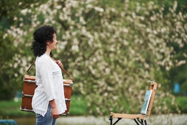 악기 케이스를 든 성숙한 화가가 아름다운 봄 공원에서 산책