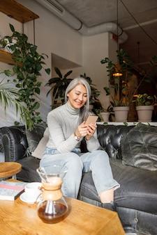カフェで成熟した淡い髪のスタイリッシュな女性のライフスタイルの肖像画