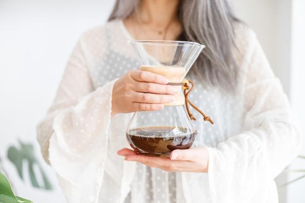 コーヒーと成熟した淡い髪のスタイリッシュな女性
