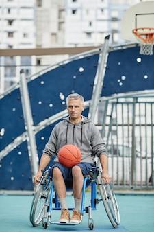 Зрелый парализованный спортсмен сидит в инвалидной коляске с мячом и смотрит в камеру