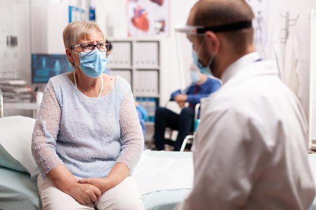 フェイスマスクを着用したcovid19の感染について医療スタッフと話している成熟した患者