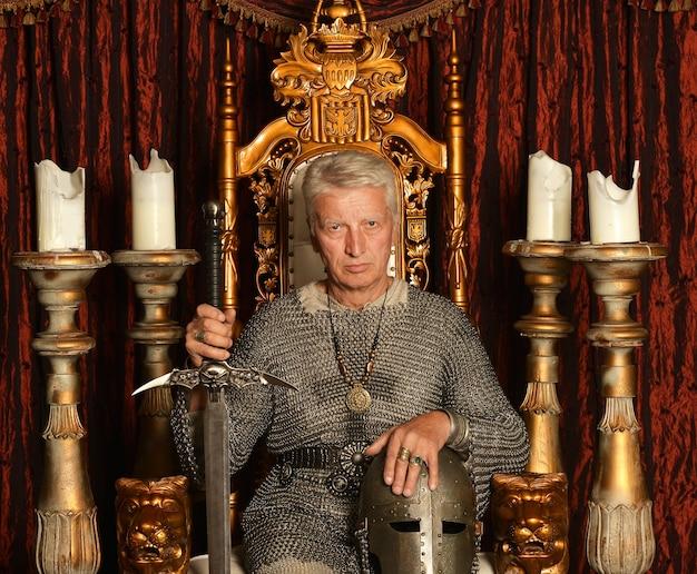 Зрелый задумчивый средневековый рыцарь на троне